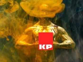 Fotografía artística de la estatuilla oscar sujetando el logo de alfombras KP