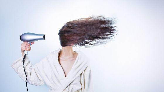 Mujer secandose el pelo con secadora